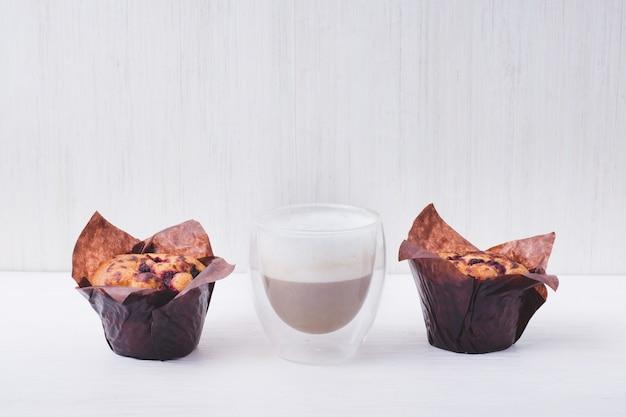 Muffin jagodowy w brązowym papierze i szkle ze smacznym mlekiem czekoladowym na białym tle, domowe wypieki.