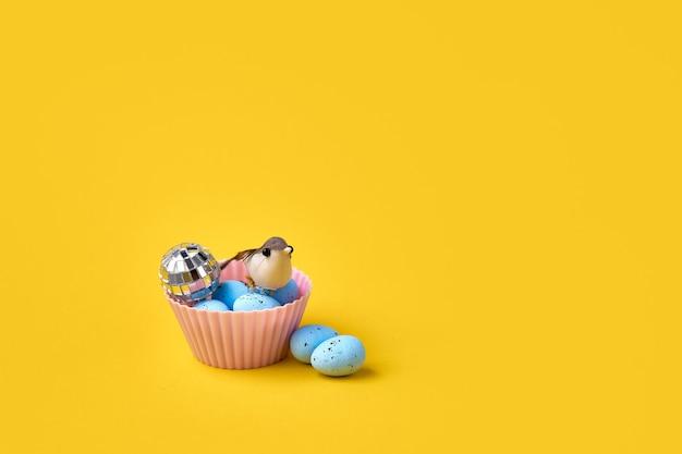 Muffin z niebieskimi jajkami wielkanocnymi i ptakiem. koncepcja wiosna. kreatywne zdjęcie koncepcyjne