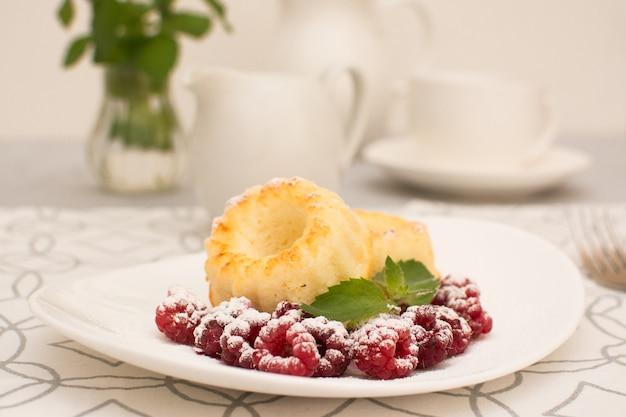 Muffinki twarogowe z malinami i miętą na białym talerzu ceramicznym.