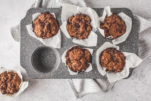 Muffiny jagodowe zdrowe wegańskie w naczyniu do pieczenia na białym tle.