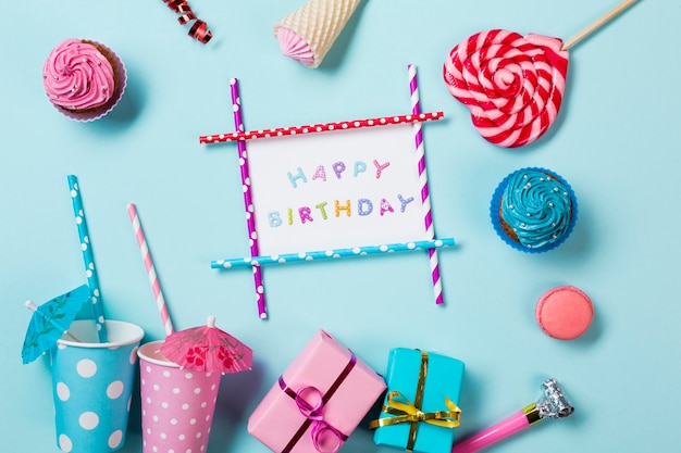 Muffiny; makaroniki; rożek waflowy; pudełka na prezenty i kubki jednorazowe na niebieskim tle