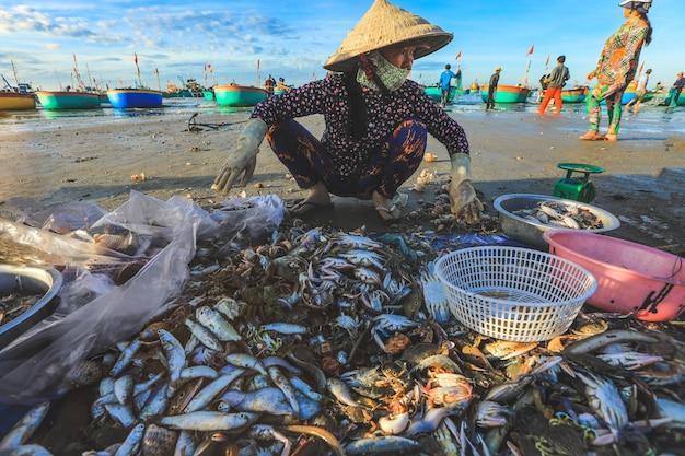 Mui ne, wietnam - 22 stycznia 2019: lokalny sprzedawca zbiera ryby i muszle w słynnej wiosce rybackiej w mui ne w wietnamie