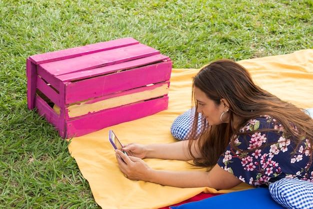 Mujer colombiana acostada en el suelo utilizando el telfono movil y sonriendo