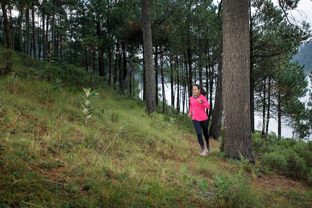 Mujer corriendo en el bosque subiendo montanas con un lago al fondo
