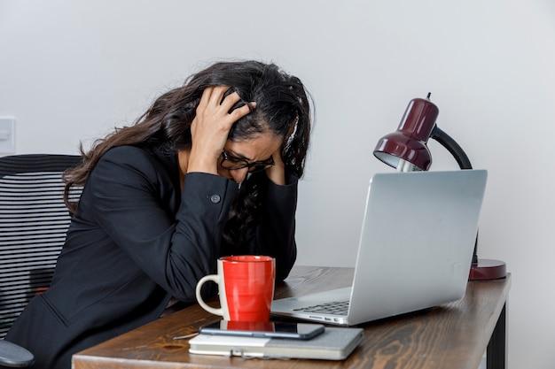 Mujer ejecutiva cansada por el exceso de trabajo en casa se lleva las manos a la cabeza