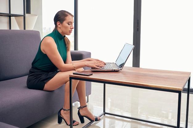 Mujer ejecutiva trabajando pl casa por pandemia pl su ordenador portatil