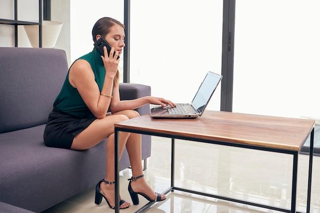 Mujer latina hablando przez telefon mientras trabaja en su casa con su computadora