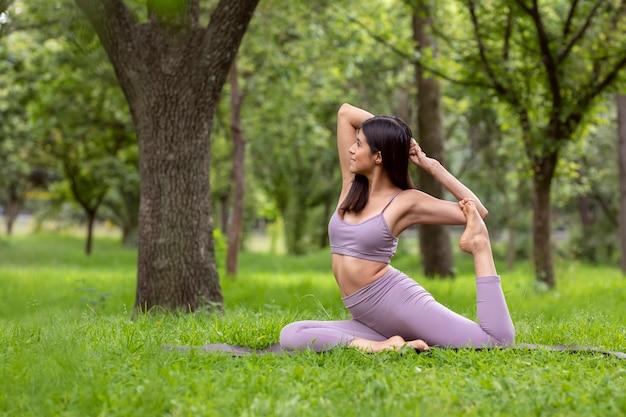 Mujer latina haciendo yogaasanas con diferentes posturas en el parque al aire libre con cesped
