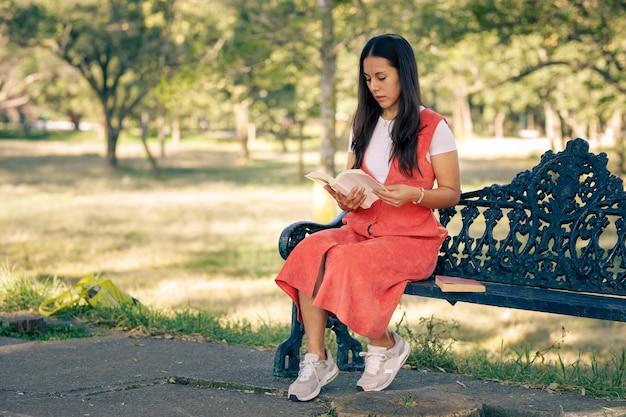Mujer latina sentada en una banca de un parque leyendo un libro