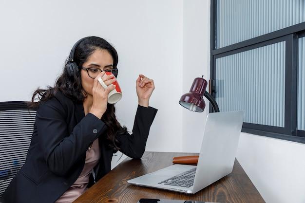 Mujer tomando una taza de cafe mientras trabaja en line desde su casa con su ordenador portatil