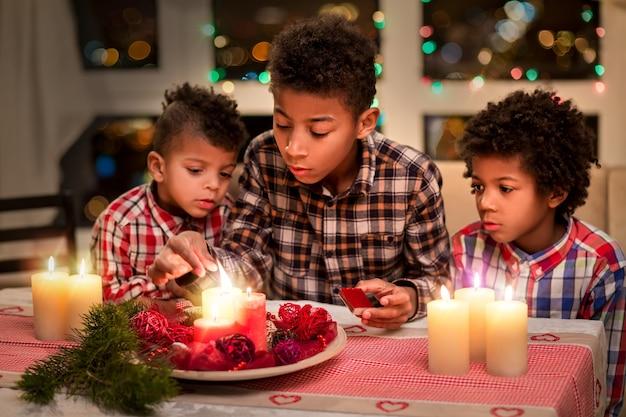 Mulat dzieci zapalające świąteczne świeczki. chłopcy zapalają świeczki z zapałkami. dekorowanie świątecznego stołu w nocy. kilka godzin przed wakacjami.