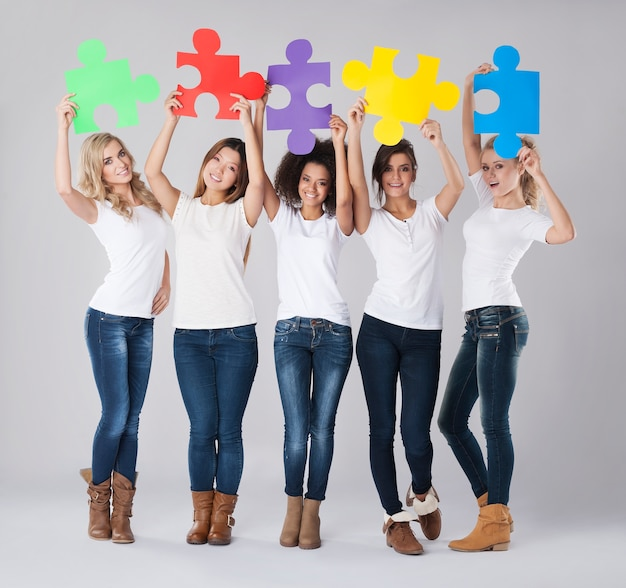 Multi etniczne dziewczyny z kolorowymi puzzlami