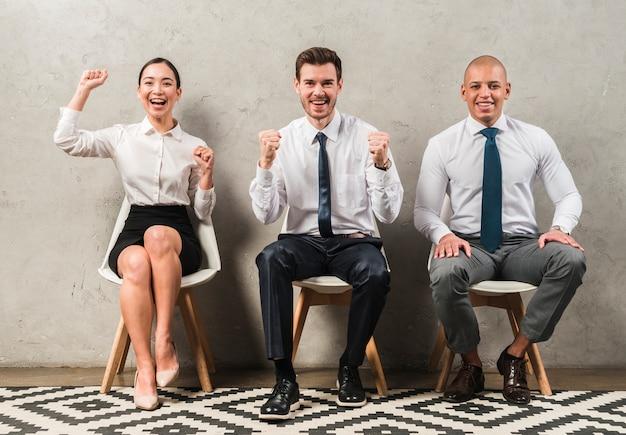 Multi etniczne młody biznesmen i businesswoman siedzi na krześle świętuje ich sukces
