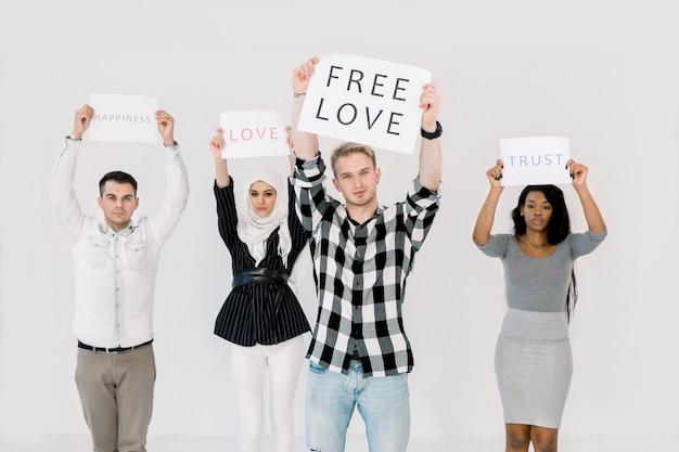 Multiethnica grupa młodych protestujących posiadających plakaty, chroniące prawa lgbt, wolna miłość, stojąca na białym tle