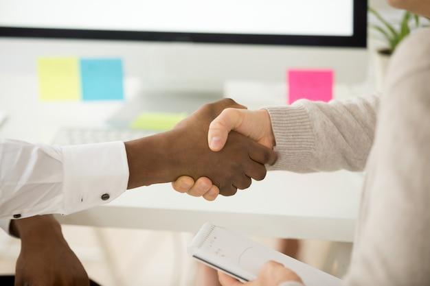 Multiracial business handshake jako koncepcja wsparcia pomocy w pracy zespołowej