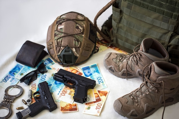 Mundur i wyposażenie wojskowe, amunicja. pancerz kuloodporny, broń, hełm kuloodporny, kajdanki, okulary przeciwsłoneczne i buty wojskowe z banknotami izraelskich nowych szekli. broń do airsoftu i protestów miejskich
