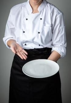 Mundur szefa kuchni z białym pustym talerzem witamy prezent danie promocja restauracji