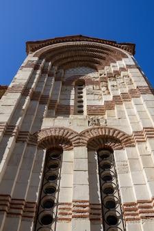 Mur starożytnego bizantyjskiego kościoła prawosławnego na tle błękitnego nieba, widok z dołu