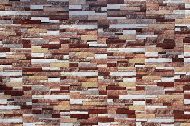 Mur z cegły o różnych fakturach, kształtach i kolorach. tło.