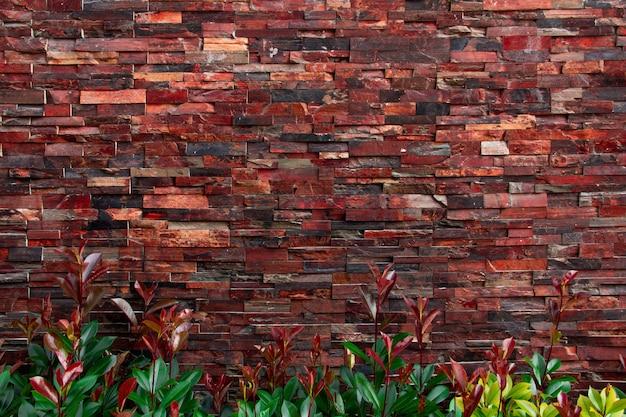 Mur z cegły o różnych fakturach, kształtach i kolorach z zielonymi roślinami na dole.