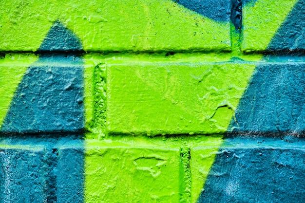 Mur z cegły z abstrakcyjnym wzorem w kolorze turkusowym i zielonym. tekstura tło