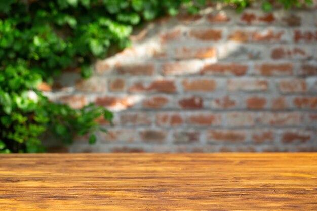 Mur z cegły z drewnianym stołem i roślinnością