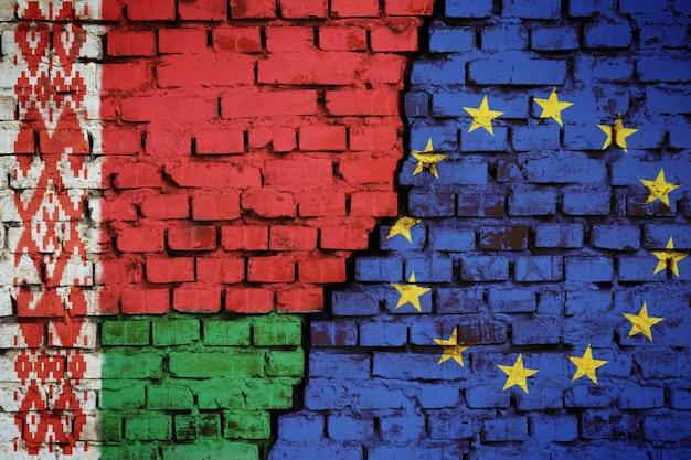 Mur z cegły z flagą białorusi i unii europejskiej