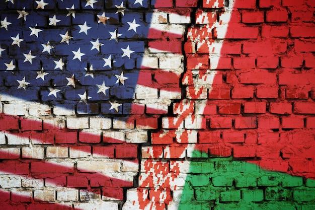 Mur z cegły z flagą białorusi i usa