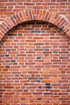 Mur z cegły z łukiem, zbliżenie ściany murowanej starego domu, fragmenty domu lub tło z czerwonej cegły. ramka na tło lub tapetę. rama pionowa
