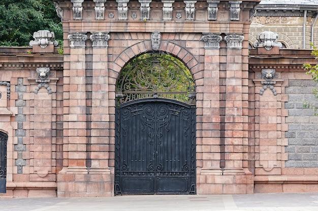 Mur z cegły z portalem i starą zamkniętą czarną żelazną bramą