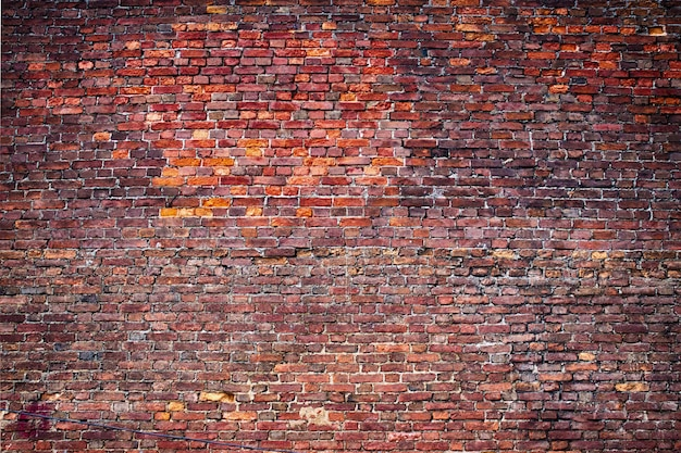 Mur z czerwonej cegły, miejska zewnętrzna powierzchnia zwietrzała jako tło