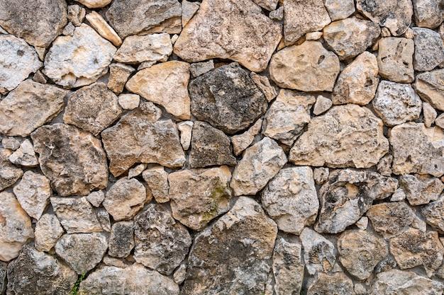 Mur z wapienia. powierzchnia jest ozdobiona naturalnym materiałem. ściana wykonana jest z dzikiego kamienia.