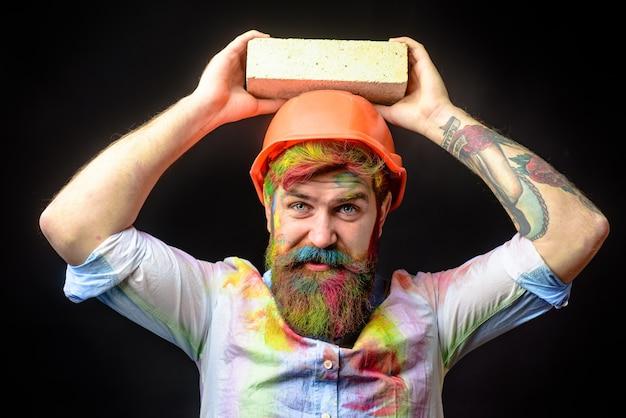 Murarz budowlany pracownik murarz człowiek budowniczy murarz w pomarańczowym kasku inżynier budownictwa zapobiega