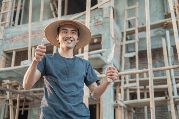 Murarz nosi uśmiechniętą czapkę z kciukami do góry i trzyma stożek cementowy w miejscu pracy