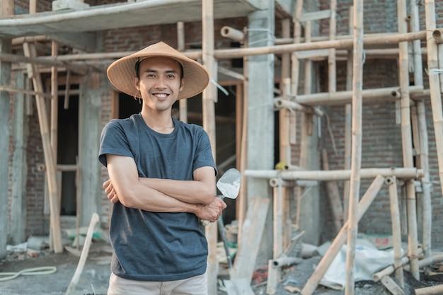 Murarz nosi uśmiechniętą czapkę ze skrzyżowanymi rękami i trzyma podczas pracy cementową warstwę