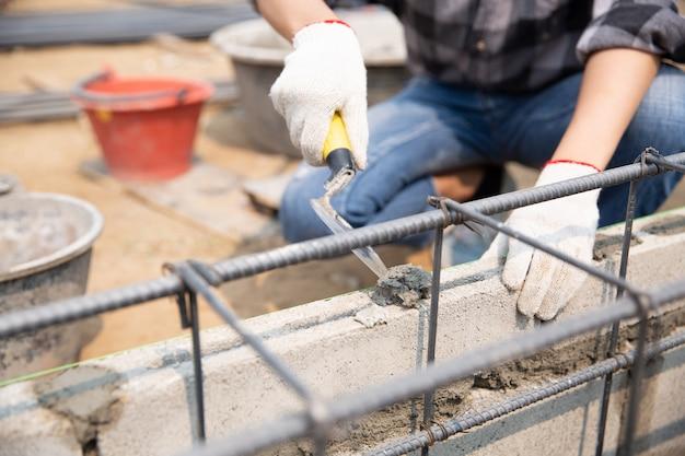 Murarz pracownik instaluje ceglanego kamieniarstwo na zewnętrznej ścianie z kielni kitu nożem