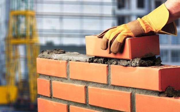 Murarz pracownik przemysłowy instalujący mur ceglany