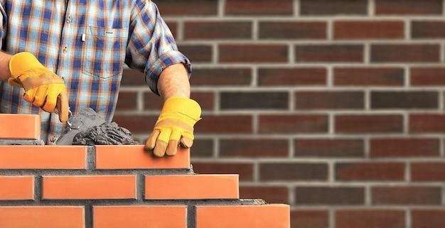 Murarz pracownik przemysłowy instalujący mur z cegły