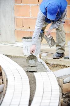 Murarz pracownik robi chodniczka brukowi z kamiennymi blokami