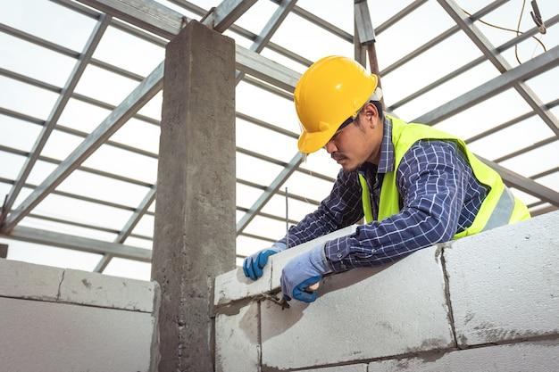Murarz pracujący z bloczkami z autoklawizowanego betonu komórkowego. murowanie, układanie cegieł na placu budowy
