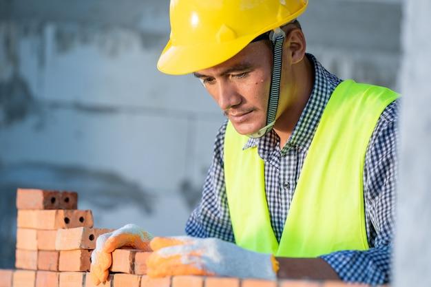 Murarz przemysłowy montujący cegły na placu budowy, murarz montujący cegły murowane.