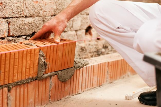 Murarz robi ścianie z cegłą i zaczynem