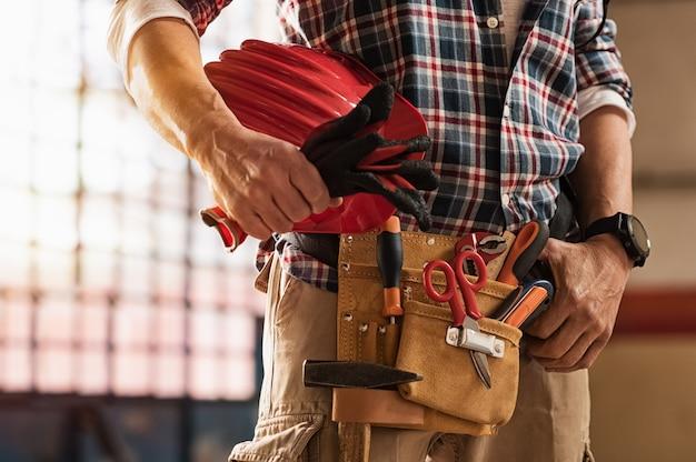 Murarz trzyma narzędzia budowlane