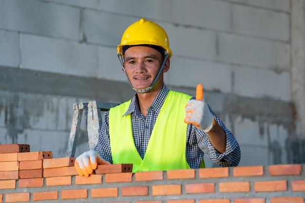 Murarz układa cegły do wykonania ściany na placu budowy.