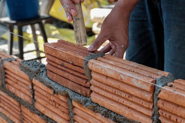 Murarza pracownik instaluje ceglanego kamieniarstwo na zewnętrznej ścianie.