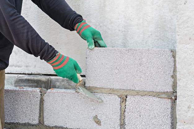 Murarza pracownik instaluje ceglanego mur na zewnętrznej ścianie z kielnia szpachelką