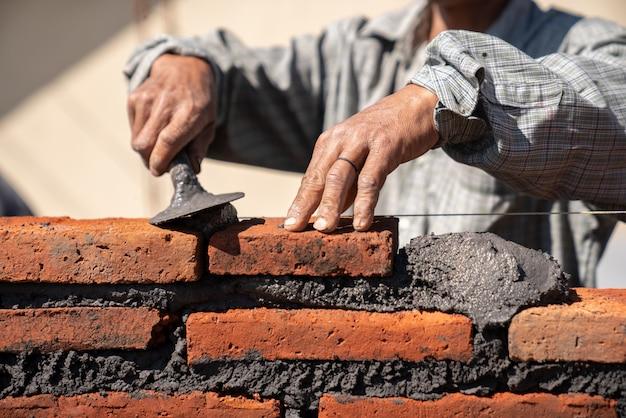 Murarza pracownik przemysłowy instaluje ceglanego kamieniarstwo z kielnia kitu nożem przy budową