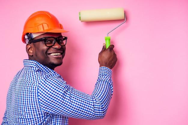 Murzyn afroamerykanin trzymający w ręku wałek do malowania maluje ścianę w różowym kolorze. szczęśliwy afrykański konstruktor obraz wewnątrz domu, biznesmen nosi kask twardy kapelusz. młody facet maluje