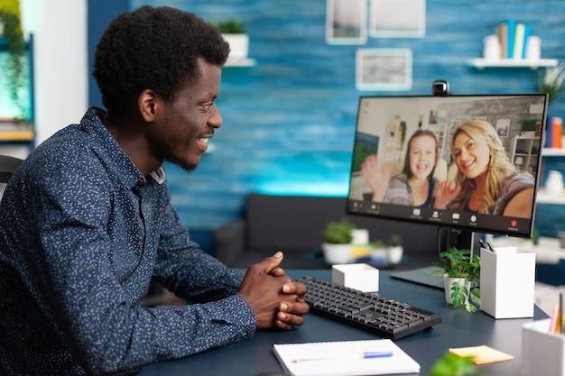 Murzyn rozmawia z przyjaciółmi i rodziną podczas rozmowy wideo