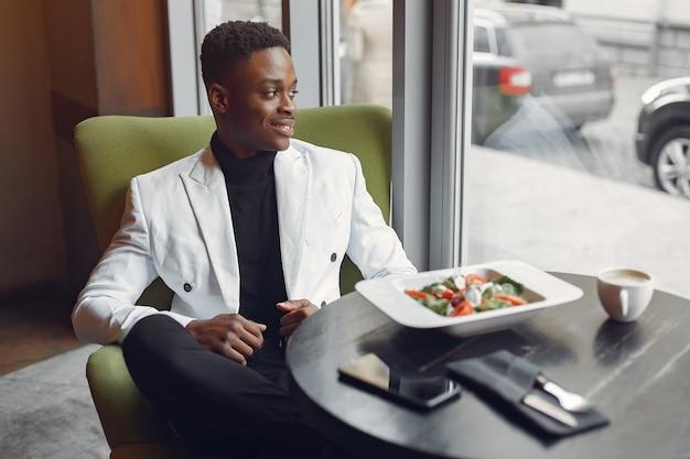 Murzyn siedzi w kawiarni i je sałatki warzywnej